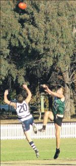 New England Nomads' Tom Hunt takes to the air with the Muswellbrook Cats' ruck