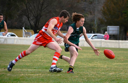 Sam Bioletti and the Swans' William Priest chasing after the ball.